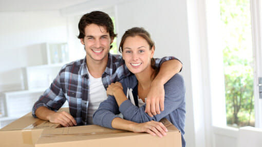 couple leaning on boxes in new home