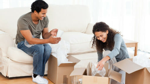 couple packing glasses into cardboard boxes